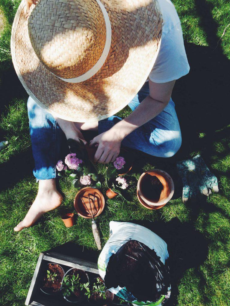 Femme qui jardine en extérieur et plante dans des pots