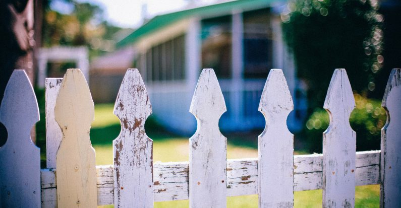 Le jardin d'une maison avec une barrière blanche devant