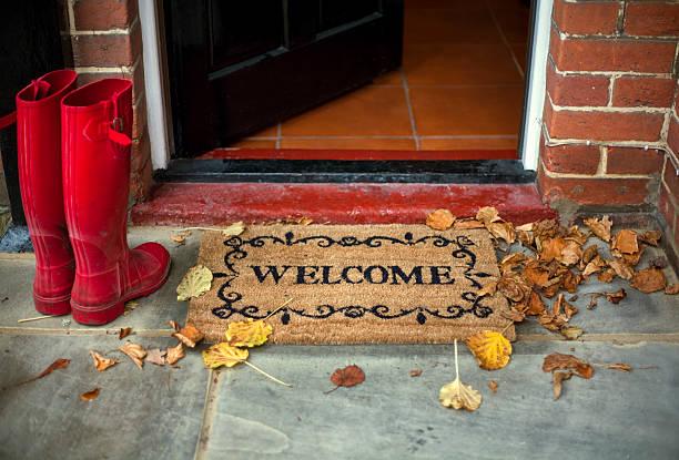 Paillasson welcome sur le perron d'une entrée décorée, avec bottes en caoutchouc rouges à côté