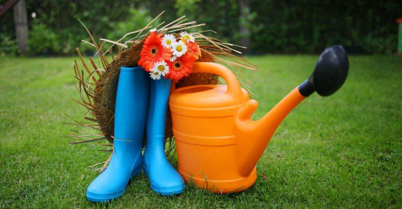 bottes en caoutchouc bleu arrosoir en plastique orange et chapeau de paille posés sur de la pelouse
