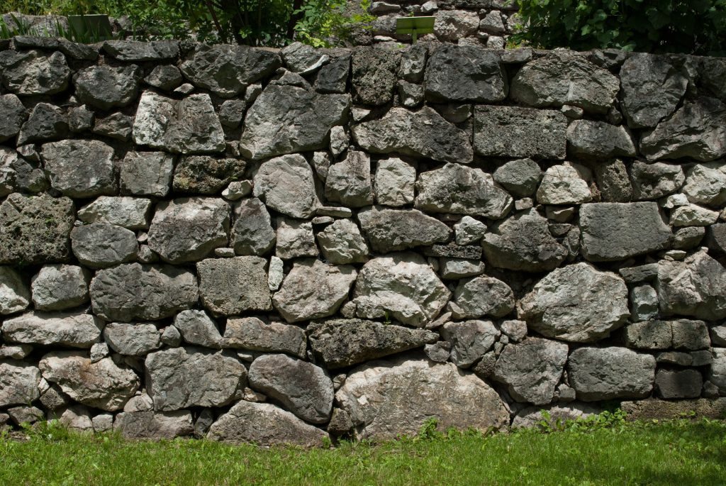 Un mur en pierres naturelles dans un jardin