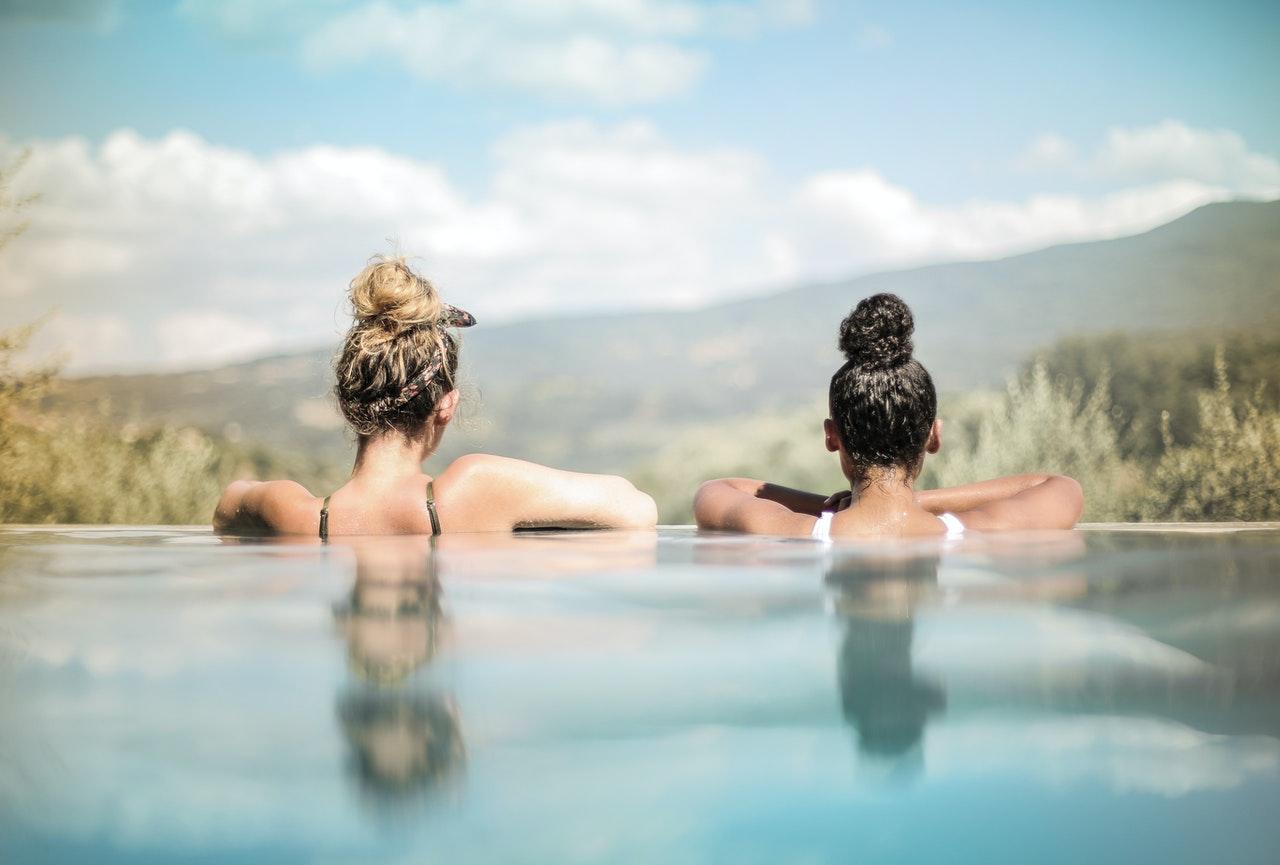 deux femmes accoudées au bord d'une piscine